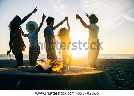 Multicultural group of friends partying on the beach - Young people celebrating during summer vacation, summertime and holidays concepts #653782066