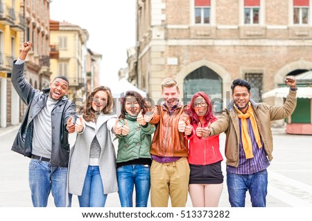 Multicultural group of friends thumbs up exulting successful day at old town square - Multiracial row of students positive attitude celebrating victory - Different skin color people united together
