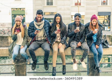 Multicultural group of friends using cellphones - Students sitting in a row and typing on the smartphones
