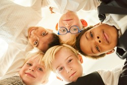 Multicultural group of kids in business outfits as happy friends in the circle