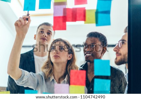 Multicultural group of male and female designers collaborating on project using colorful stickers with ideas for productive work.Positive colleagues reading notes written on papers glued on glass wall