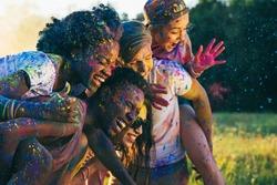 multicultural happy friends piggybacking together at holi festival