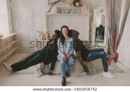 Multicultural love and relationships concept. Young white woman sits between two sleeping african dark skinned men. Soft focus studio portrait of interracial embracing couple. Interracial friendship.