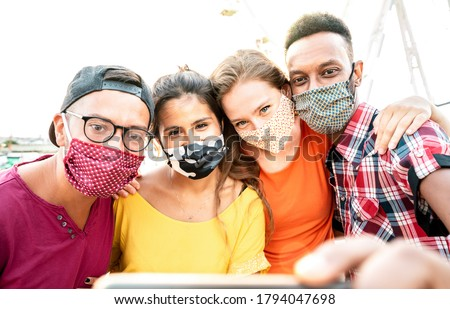 Multicultural milenial travelers taking selfie with closed face masks - New normal travel concept with young people having safe fun together at ferris wheel - Bright warm sunshine filter