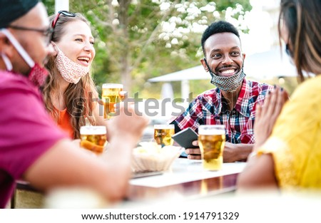 Multicultural people drinking beer with open face masks - New normal gathering concept with friends having fun together on happy hour at brewery bar - Bright filter with focus on afroamerican guy Stock photo ©