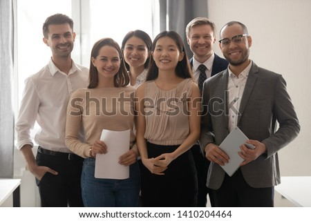 Multicultural professional work team happy company employees group looking at camera stand in office, smiling diverse corporate staff workers business people posing together, human resource portrait
