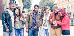 Multicultural row of  friends walking together holding mobile smart phone outdoors - Interracial happy couples having fun day at city centre   - Friendship and modern technology concept - Vintage filt