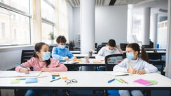 Multicultural schoolchildren wearing disposable medical masks sitting at table in classroom, keeping new normal social distance, looking at each other, studying at elementary school and writing
