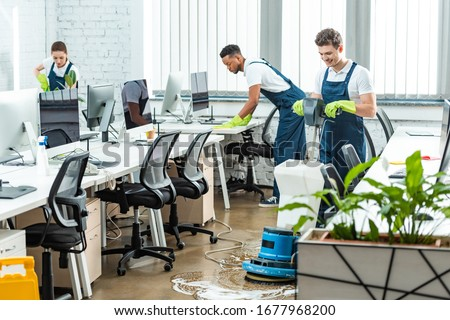 multicultural team of cleaners working in modern open space office