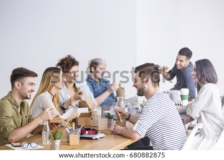 Multicultural team of coworkers eating a healthy lunch together at the office