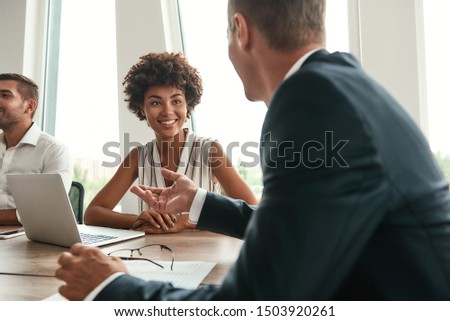 Multicultural team. Young and beautiful afro american woman discussing something with colleagues and smiling while sitting in the modern office