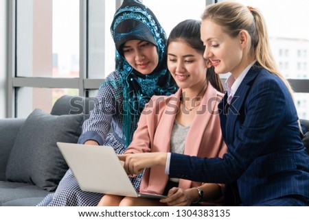 Multicultural working group. Team of businesswomen of different ethnicity, Caucasian, Asian and Arabic working together with laptop computer at office workplace. Multiethnic teamwork concept.