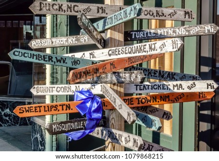 Multidirectional street sign with pointers to distant towns and unincorporated communities, some with odd names, for themes of tourism and Americana #1079868215