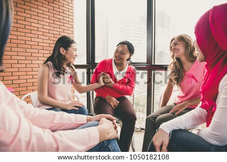 Multiethinic women wearing pink color clothes sitting in circle talking and meeting for breast cancer awareness campaign