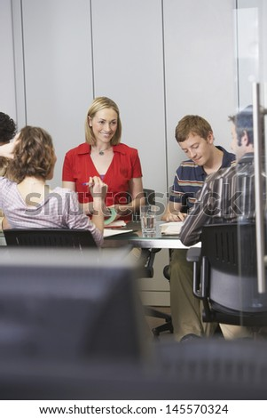 Multiethnic business executives sitting around conference table - stock photo