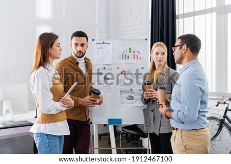 Multiethnic business people with takeaway coffee and digital tablet working near flipchart stock photo