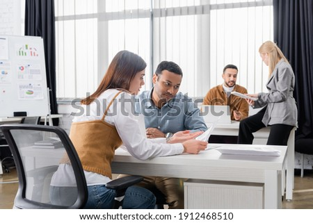 Multiethnic business people working with papers near colleagues in office stock photo