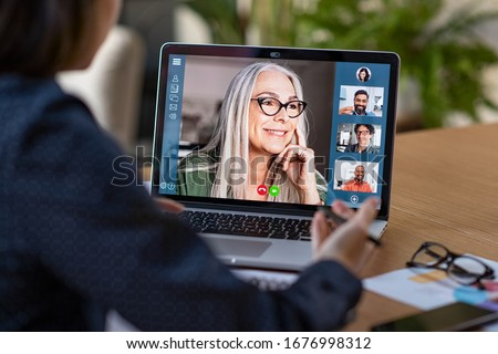 Photo of  Multiethnic business team having discussion in video call. Rear view of business woman in video conference with boss and his colleagues during online meeting. Senior woman in video call with partners.