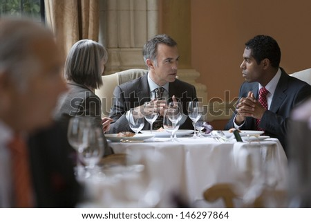 Multiethnic businesspeople sitting at restaurant table and talking