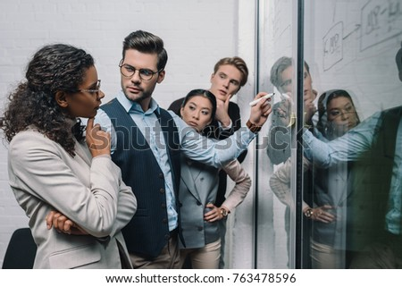multiethnic businesspeople writing on glass board and working in office #763478596