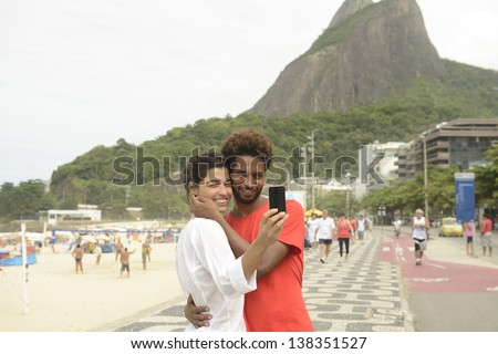Multiethnic couple photographing themselves with mobile phones on the board walk of Ipanema beach in Rio de Janeiro, Brazil.