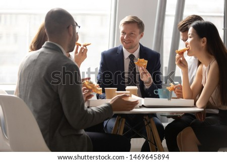 Multiethnic coworkers talk and chat having Italian fast food takeaway delivery service in office, diverse coworkers have fun communicating eating tasty pizza spending lunch break together #1469645894