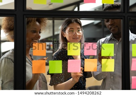 Multiethnic creative diverse young business team people three colleagues students group brainstorm on work plan talk write ideas tasks on post it sticky notes look at glass at scrum teamwork briefing