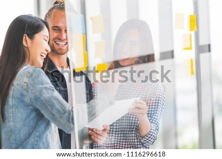 Multiethnic diverse group meeting write project plan together on transparent glass board, happy candid smile. Small business startup, teamwork discussion, team building, or strategy brainstorm concept