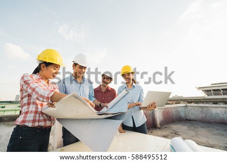Multiethnic diverse group of engineers or business partners at construction site, working together on building's blueprint, architect industry or teamwork concept. #588495512