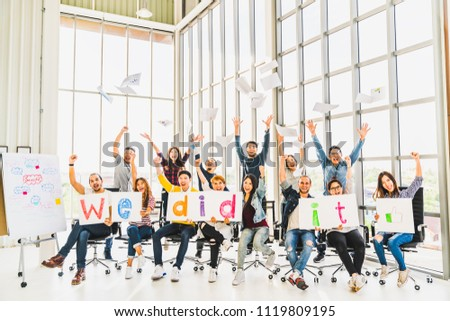 Multiethnic diverse group of happy business people cheering together, celebrate project success with papers wrote words We did it. Coworkers teamwork, career job achievement, or small business concept