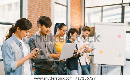Multiethnic diverse group of happy young adult using information technology gadget devices together. Modern lifestyle culture, casual business, creative people, education, social media network concept stock photo