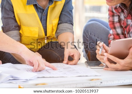 multiethnic diverse team of engineers discussing about new project in city, engineer man and woman work with blueprint in front of building, business people co-working teamwork concept,focus on hand
