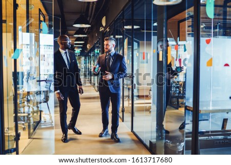 multiethnic entrepreneurs in elegant clothes developing strategic plans for future collaboration walking along corridor against glass walls with colorful spots and reflection in contemporary office