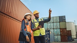 Multiethnic Female Industrial Engineer with Tablet and Black African American Male Supervisor in Hard Hats and Safety Vests Stand in Container Terminal. Colleagues Talk About Logistics Operations.
