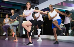 Multiethnic group of adult people practicing active dancing in class at fitness center