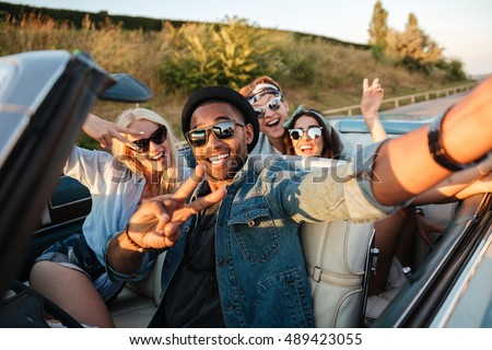 Multiethnic group of cheerful young people taking selfie in the car #489423055
