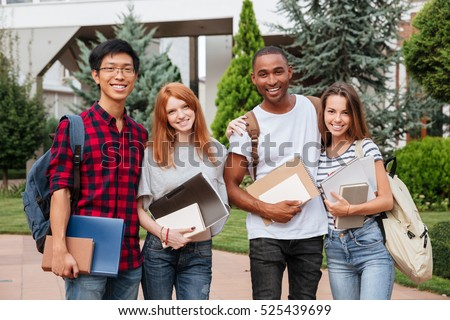 Multiethnic group of cheerful young students standing together outdoors