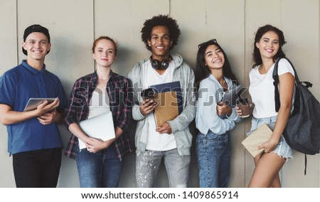 Multiethnic group of cheerful young students standing together outdoors, panorama