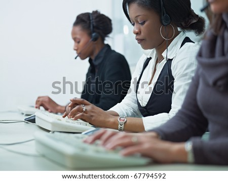 multiethnic group of female customer service representatives talking on the phone and typing on computer keyboard. Horizontal shape, side view, copy space - stock photo