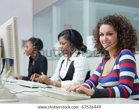 multiethnic group of female customer service representatives talking on the phone, with woman looking at camera. Horizontal shape, side view