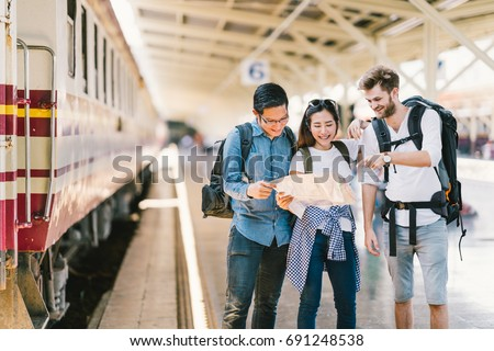 Multiethnic group of friends, backpack travelers, or college students using local map navigation together at train station platform. Asia travel destination, tourism activity, or railroad trip concept - Shutterstock ID 691248538