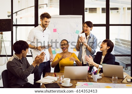 Multiethnic group of happy business people working together, meeting and brainstorming in office. Use computer, laptop, tablet, mobile phone.