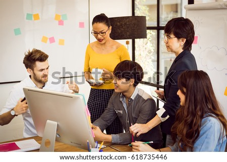 Multiethnic group of happy business people working together, meeting and brainstorming in office. Use computer, laptop, tablet, mobile phone. #618735446