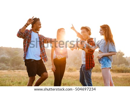 Multiethnic group of happy young friends drinking beer and soda and having fun outdoors