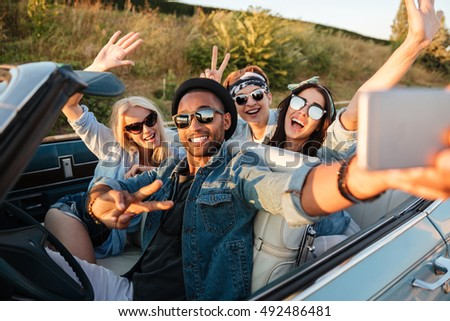 Multiethnic group of happy young people taking selfie with smartphone and showing peace sign in the car #492486481
