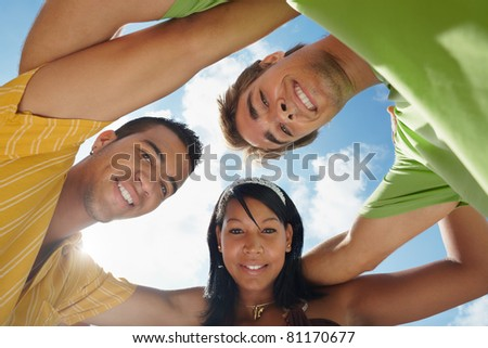 multiethnic group of male and female friends hugging and looking at camera with sky in background. Low angle view