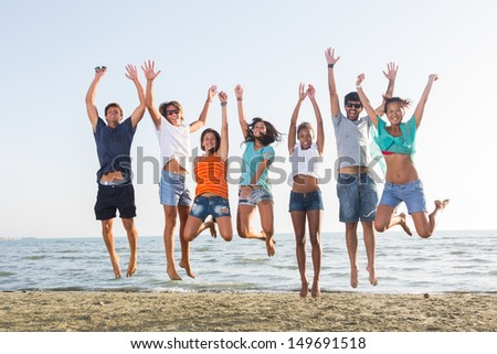 Multiethnic Group of People Jumping at Beach