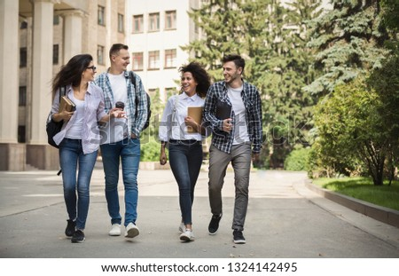 Multiethnic group of smiling students walking together walking near college