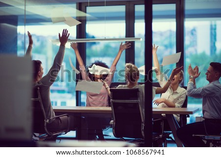 multiethnic Group of young business people throwing documents and looking happy while celebrating success at their working places in night office #1068567941