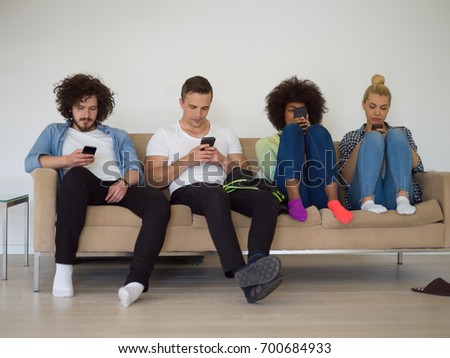 multiethnic group of young people sitting on a sofa at home,staring at smartphone, being antisocial, smartphone addiction - Shutterstock ID 700684933
